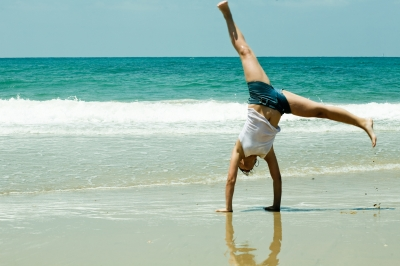 Athletic woman doing a cartwheel on the ocean beach