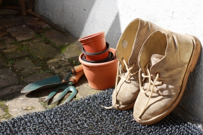 Garden shoes and tools resting against wall